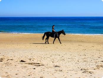 femme qui fait du cheval sur la plage
