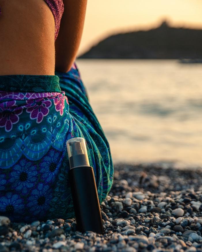 femme à la plage avec de la crème solaire