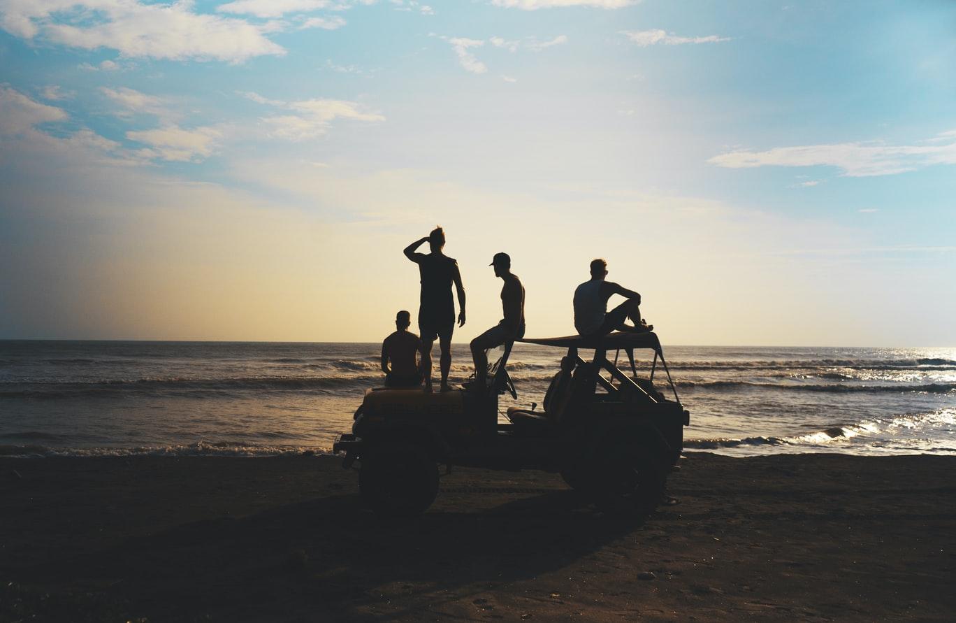 groupe de personnes sur une voiture de location à côté de la mer